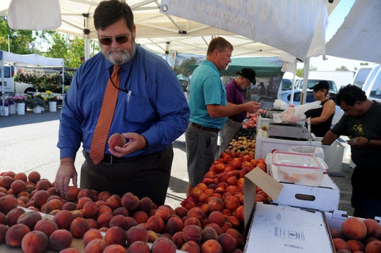 Ed Williams, agricultural commissioner for the county of Ventura looks at some peaches at the farmer's market in Thousand Oaks. Williams was named the county's new commissioner in July.