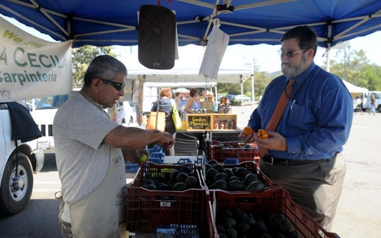 Oliverio Castrejon, (left), who works for Rancho Santa Cecilia,  talks with Ed Williams, agricultural commissioner for the county of Ventura, at the Thousand Oaks Farmer's Market. Williams was looking at some avocados.