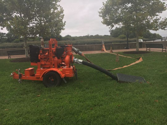 Delaware City uses pumps to drain water from the town into the Delaware River Monday.