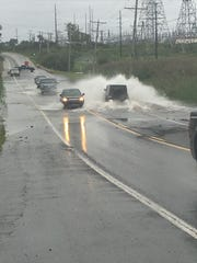 Cars wade through the deep water on Del. 9 Monday evening as rain collects near the Delaware Refinery in Delaware City.