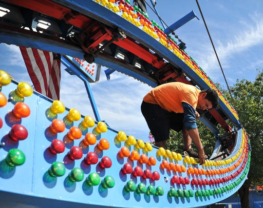 Jose Luis works to replace light bulbs on one of several rides that will fill the MPEC parking lot for the Texas/Oklahoma Fair. The fair will run through September 15.