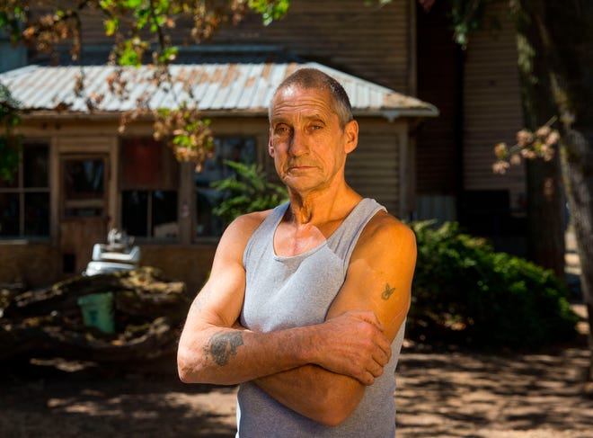 in this Aug 28, 2018 photo, filbert farmer Wayne Wise poses in Eugene Ore. Wise was mowing in his filbert orchard on July 15, when a piece of barbed wire was shredded by his mulcher, sending a piece of shrapnel into his side. He worked another half hour until his shirt soaked through with blood. He then drive himself to the hospital where doctors discovered the shrapnel had passed through his lung and lodged between the chambers of his heart. Emergency open heart surgery saved his life. (Brian Davies/The Register-Guard via AP)