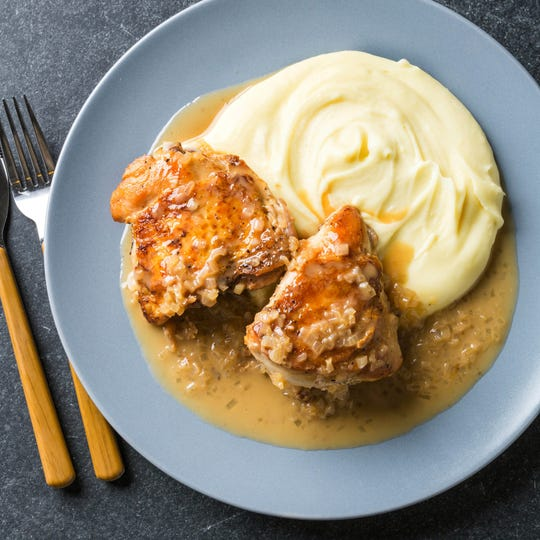 """This undated photo provided by America's Test Kitchen in August 2018 shows pan-roasted chicken breasts with shallot-thyme sauce in Brookline, Mass. This recipe appears in the cookbook """"How to Roast Everything."""