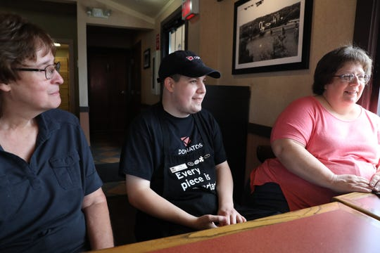 Jake Dewart sits with his mother Pennie, right, and manager Connie Deckard at Donatos Pizza in Zanesville.
