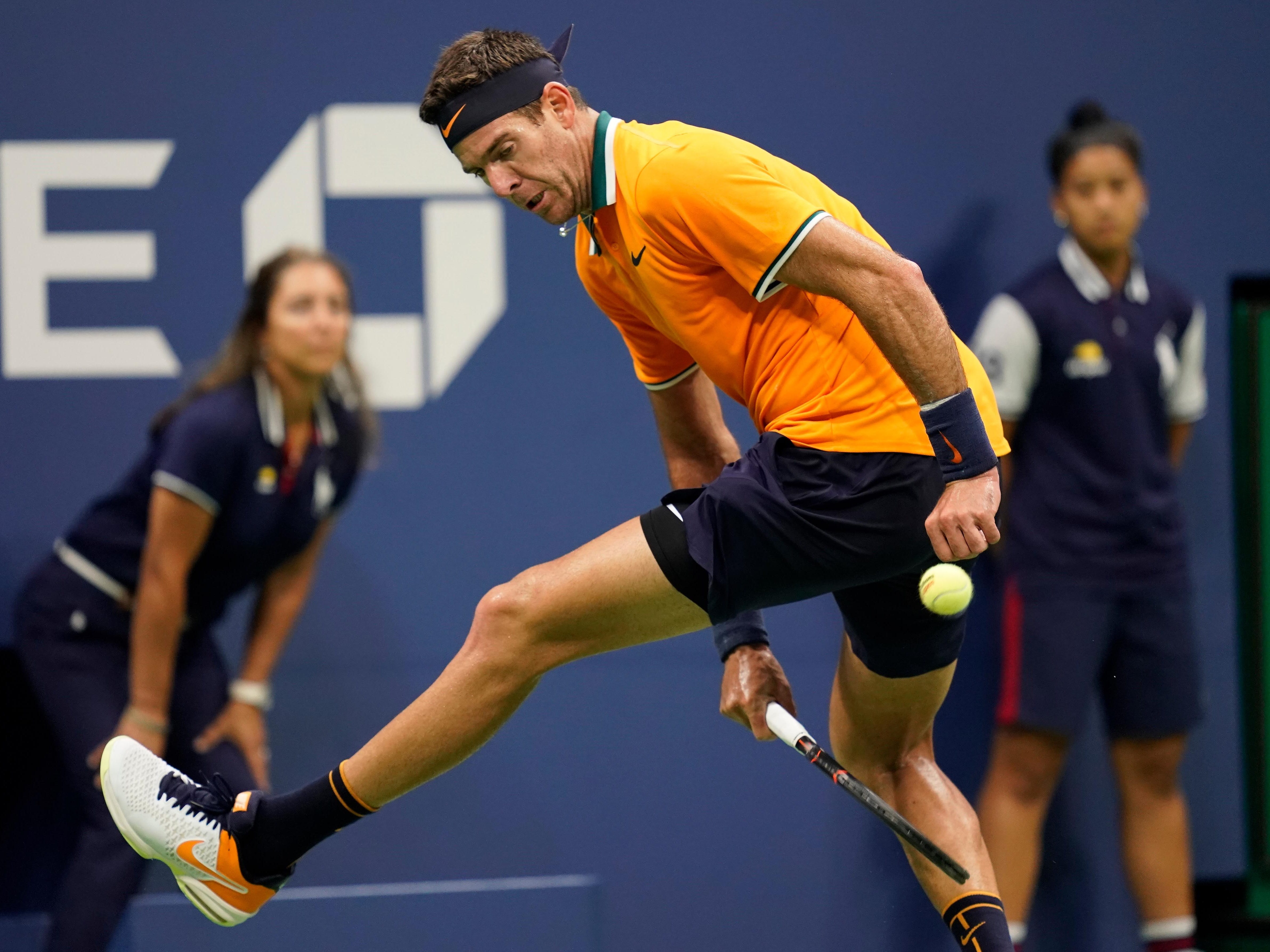 Juan Martin del Potro plays a shot between his legs against Novak Djokovic.