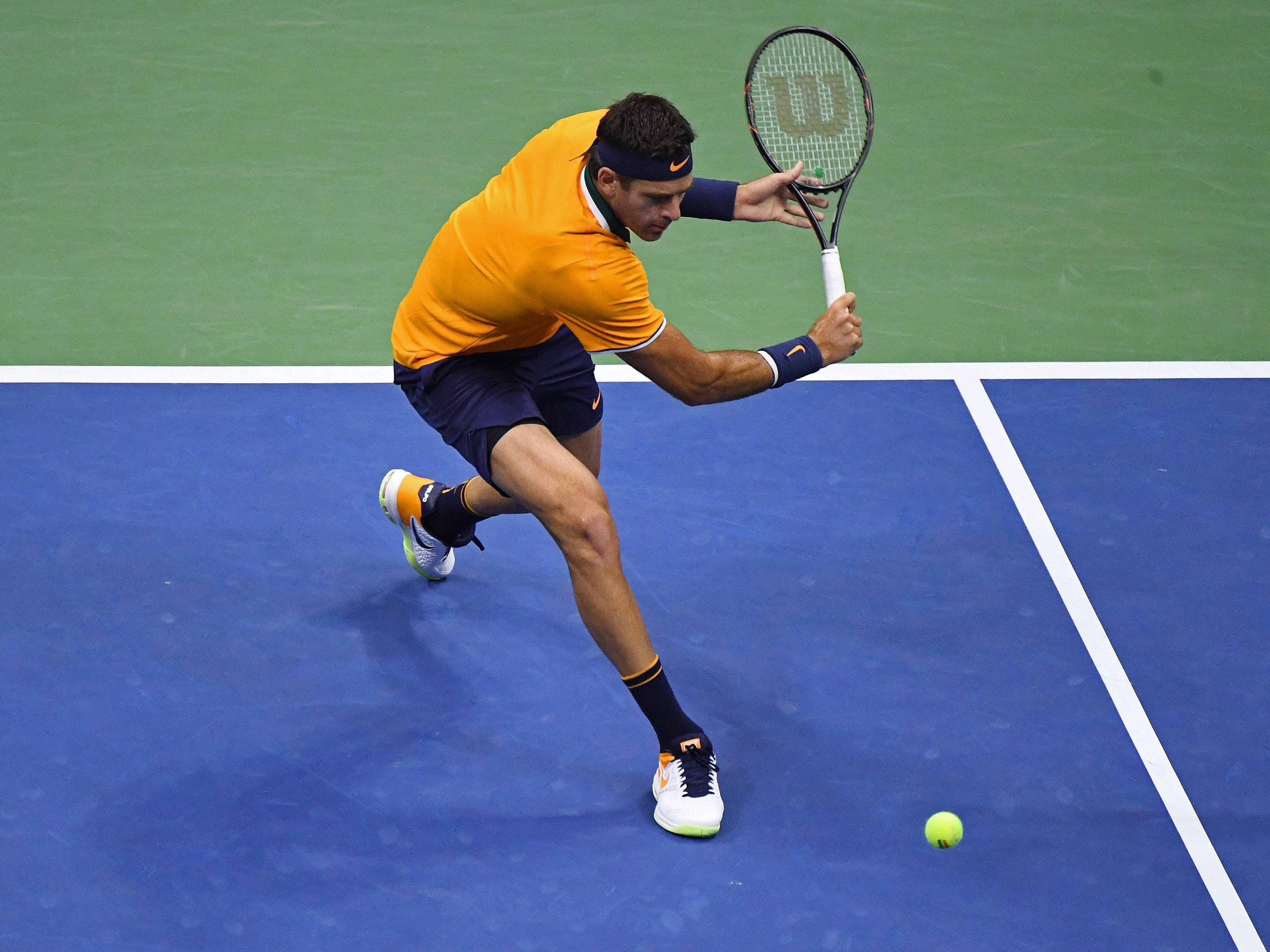 Juan Martin del Potro plays a backhand against Novak Djokovic.