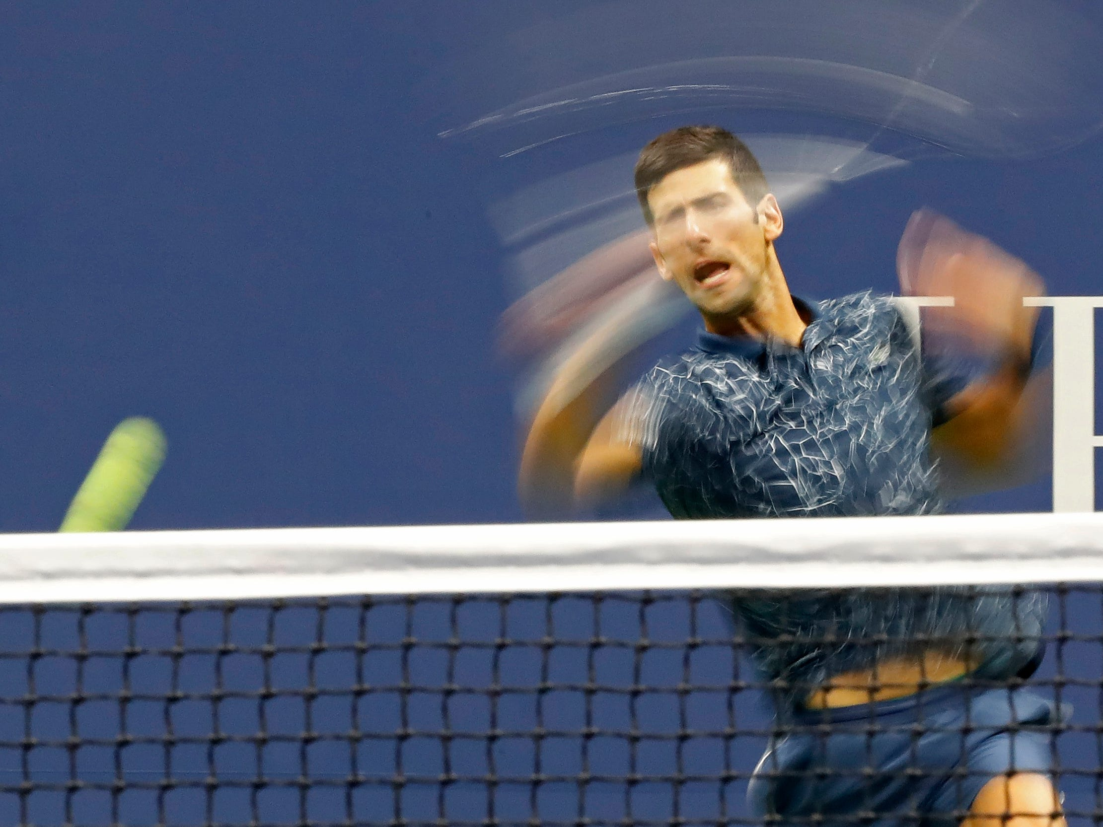 Novak Djokovic plays a forehand against Juan Martin del Potro.