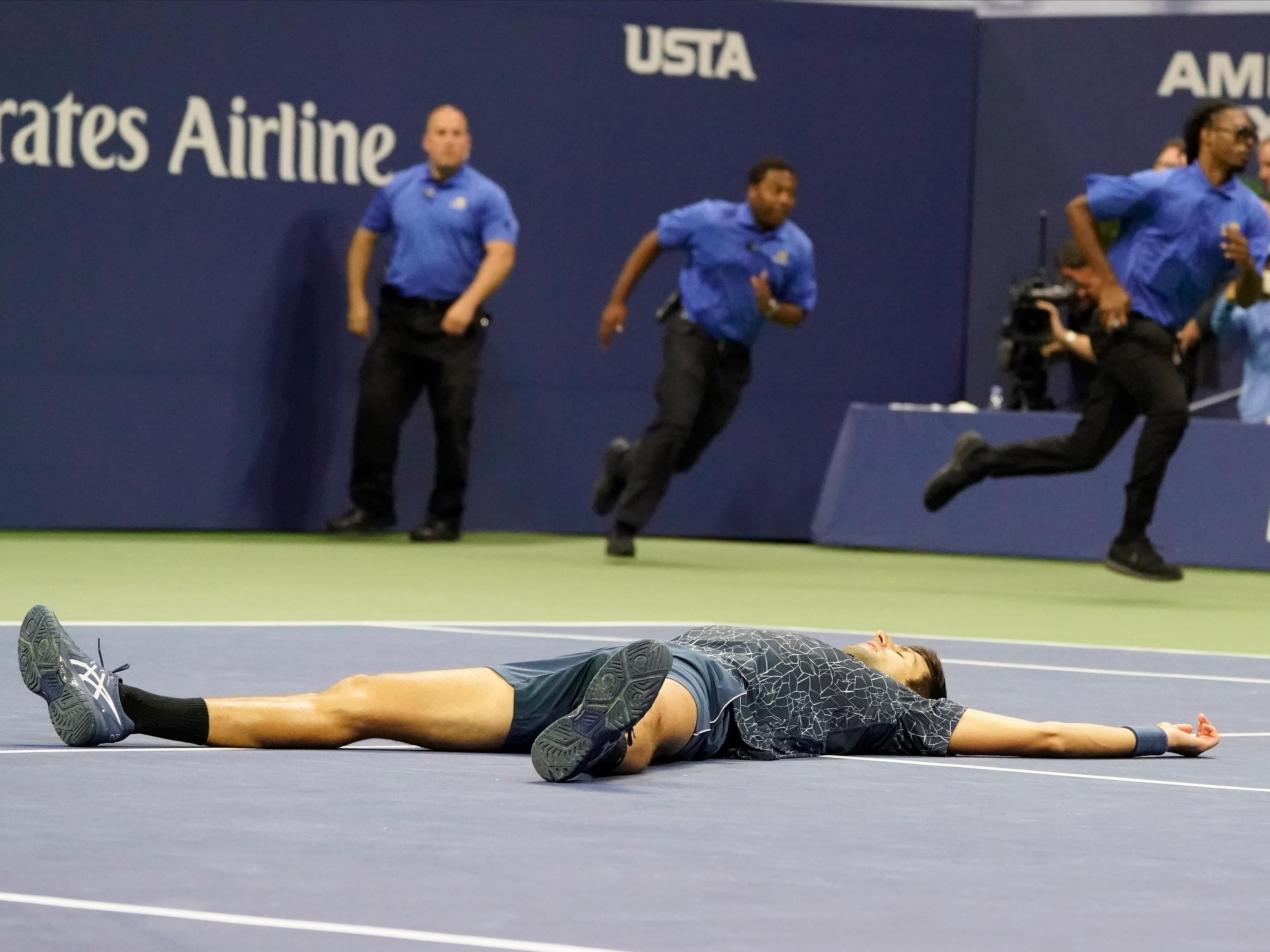 Novak Djokovic falls to the ground in celebration after defeating Juan Martin del Potro.