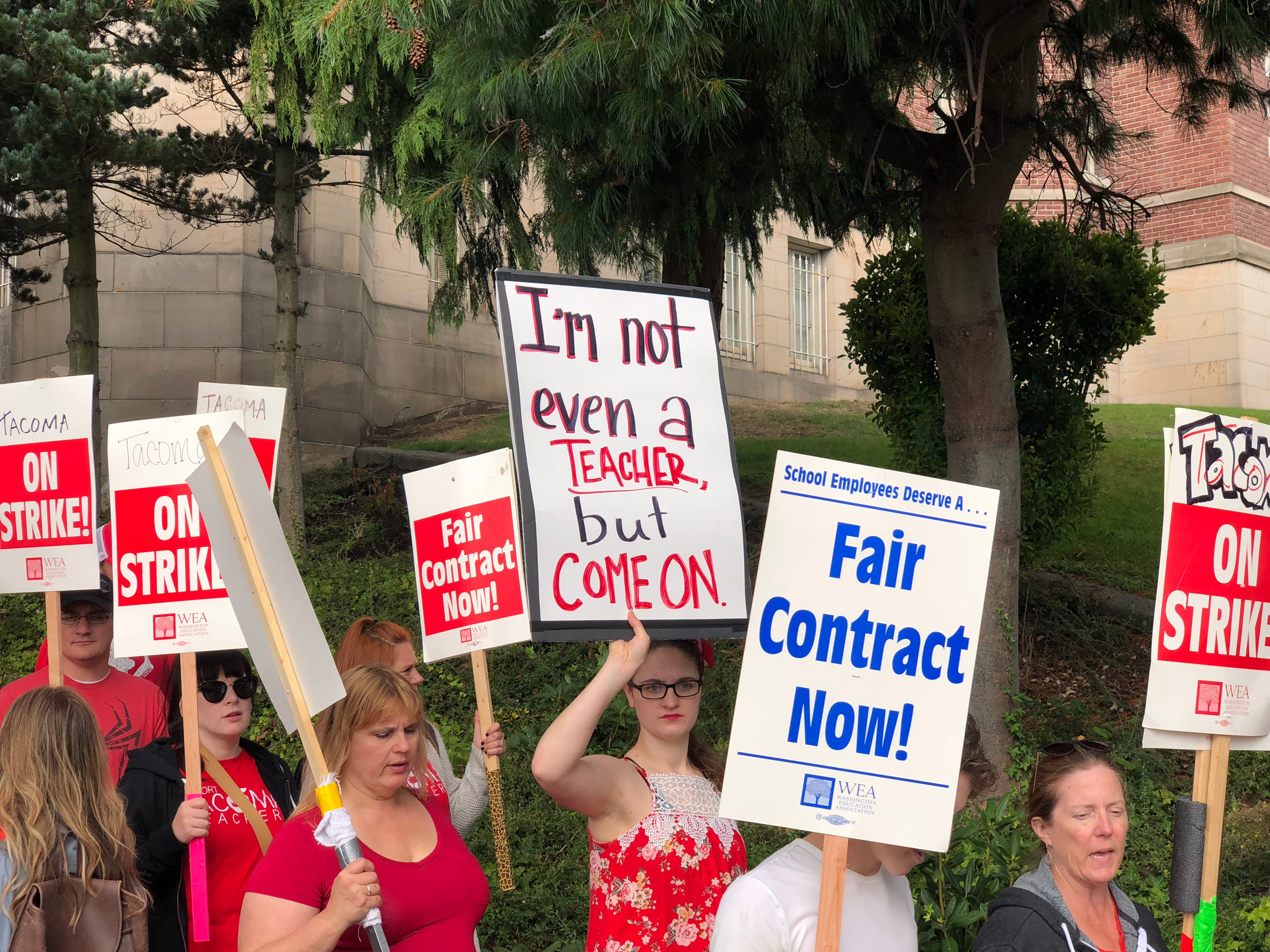 Striking teachers carry picket signs as they march in front of the Tacoma School District Central Administration Building, Monday, Sept. 10, 2018, in Tacoma, Wash.