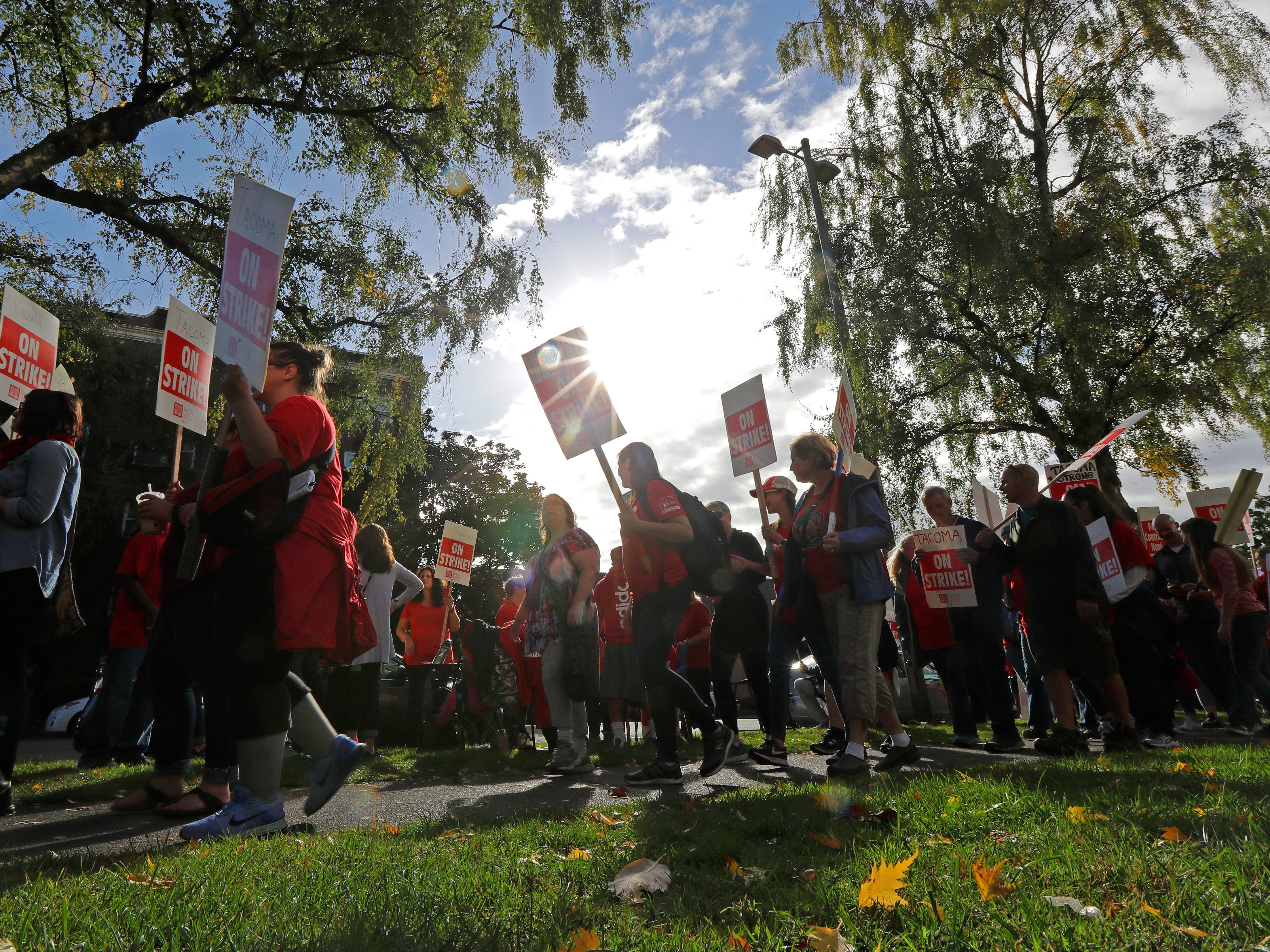 Striking teachers carry picket signs as they march around the Tacoma School District Central Administration Building, Monday, Sept. 10, 2018, in Tacoma, Wash.