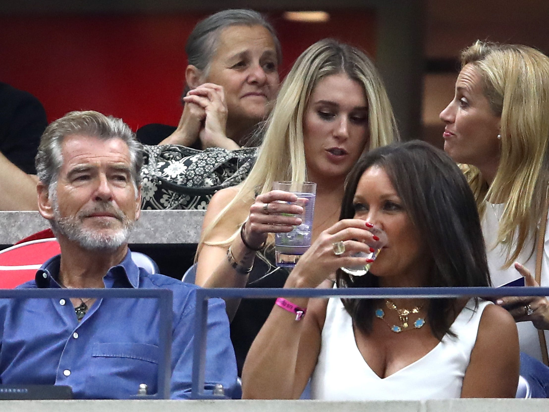 Actor Pierce Brosnan, front left, and actress/singer Vanessa Williams, second from left, watch the women's final between Serena Williams and Naomi Osaka.