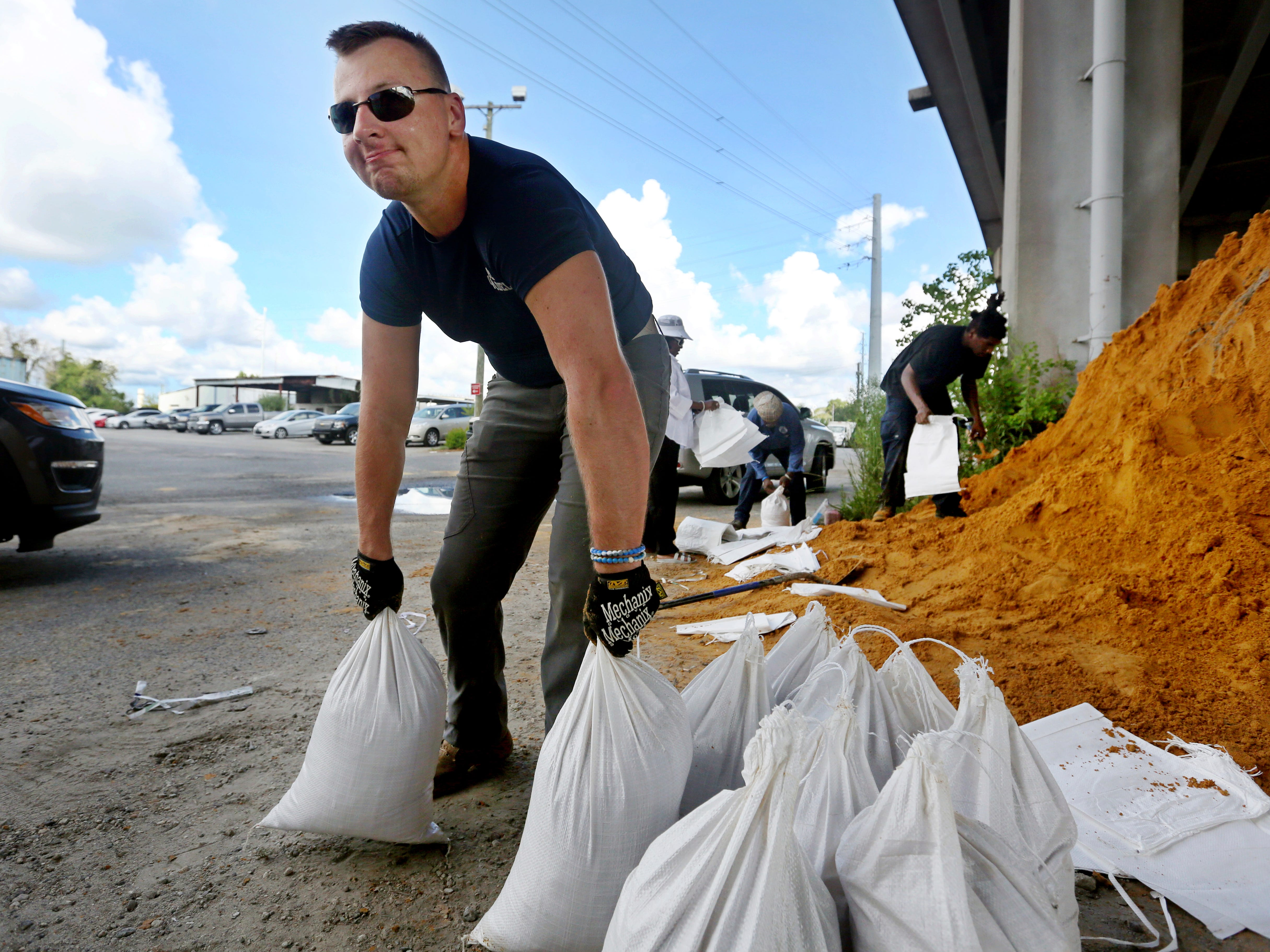 Kevin Orth loads sandbags into cars on Milford Street as he helps residents prepare for Hurricane Florence, Monday, Sept. 10, 2018, in Charleston, S.C.