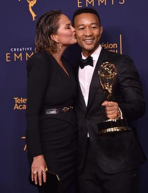 Chrissy Teigen lays a congratulatory smooch on husband John Legend after he won his first Emmy Sunday, joining the EGOT club.