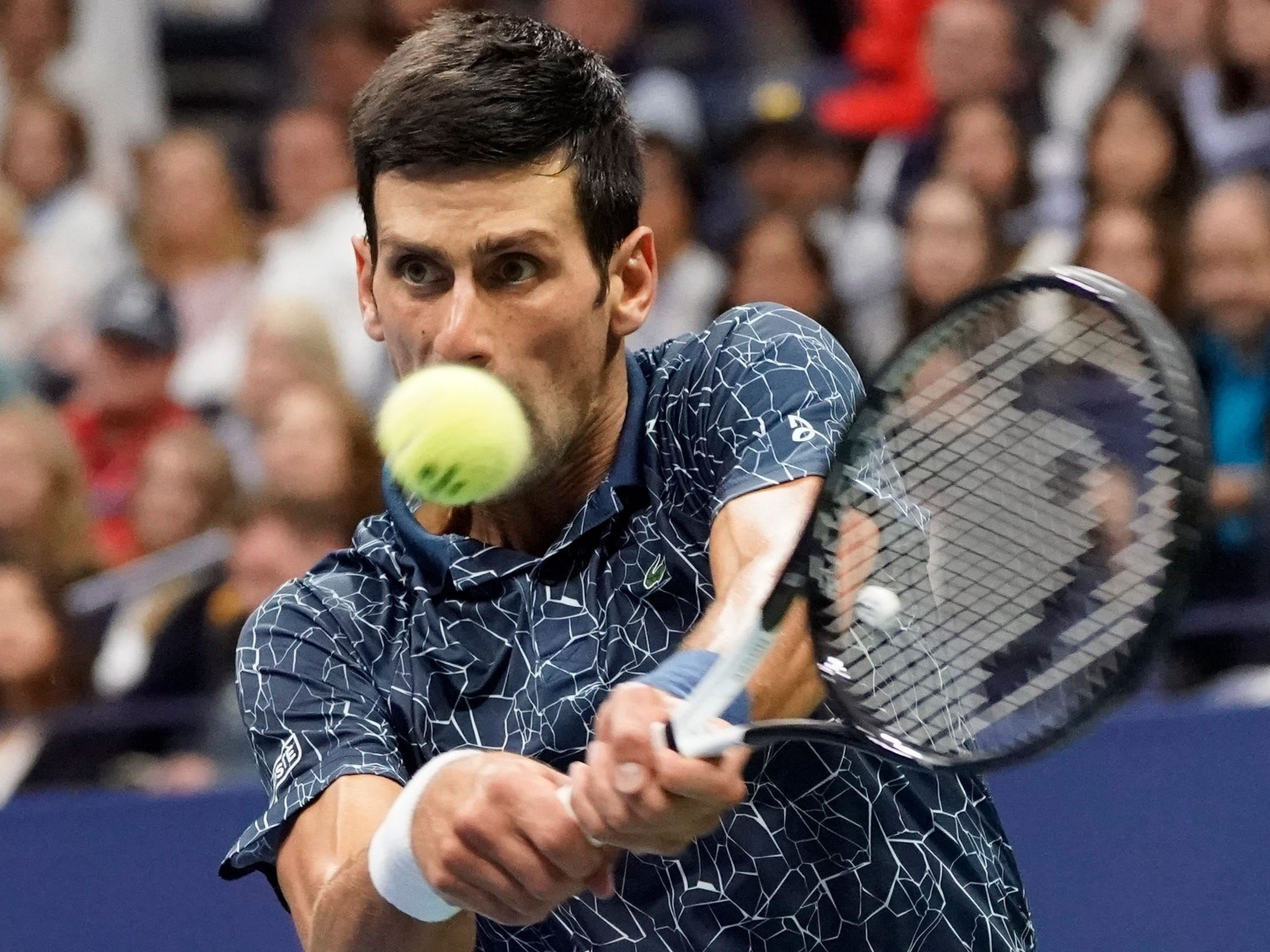Novak Djokovic plays a backhand return Juan Martin del Potro.