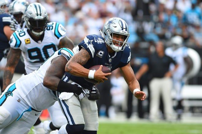 Dallas Cowboys quarterback Dak Prescott (4) is sacked by Carolina Panthers defensive tackle Kawann Short (99) in the second quarter at Bank of America Stadium.
