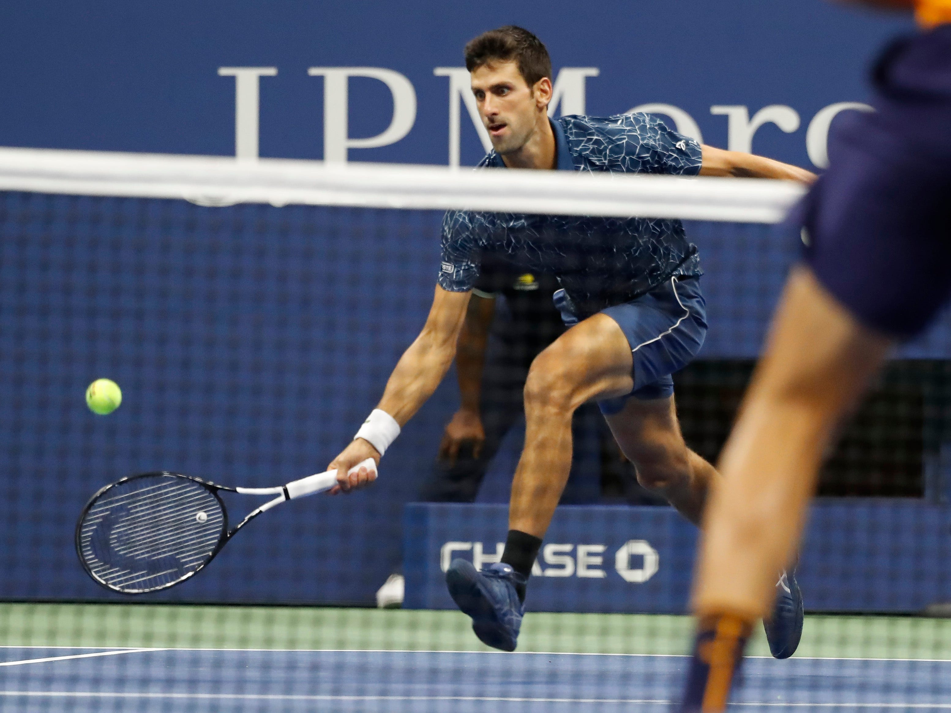 Novak Djokovic reaches for a forehand return against Juan Martin del Potro.