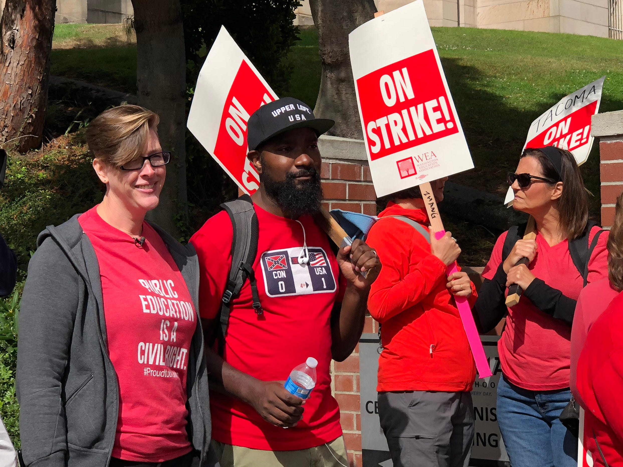 Nate Bowling, the 2016 Washington teacher of the year who works in the Tacoma School District, walks the picket line with Mandy Manning, the 2018 Washington teacher of the year, who flew in from Spokane to support her fellow teachers.