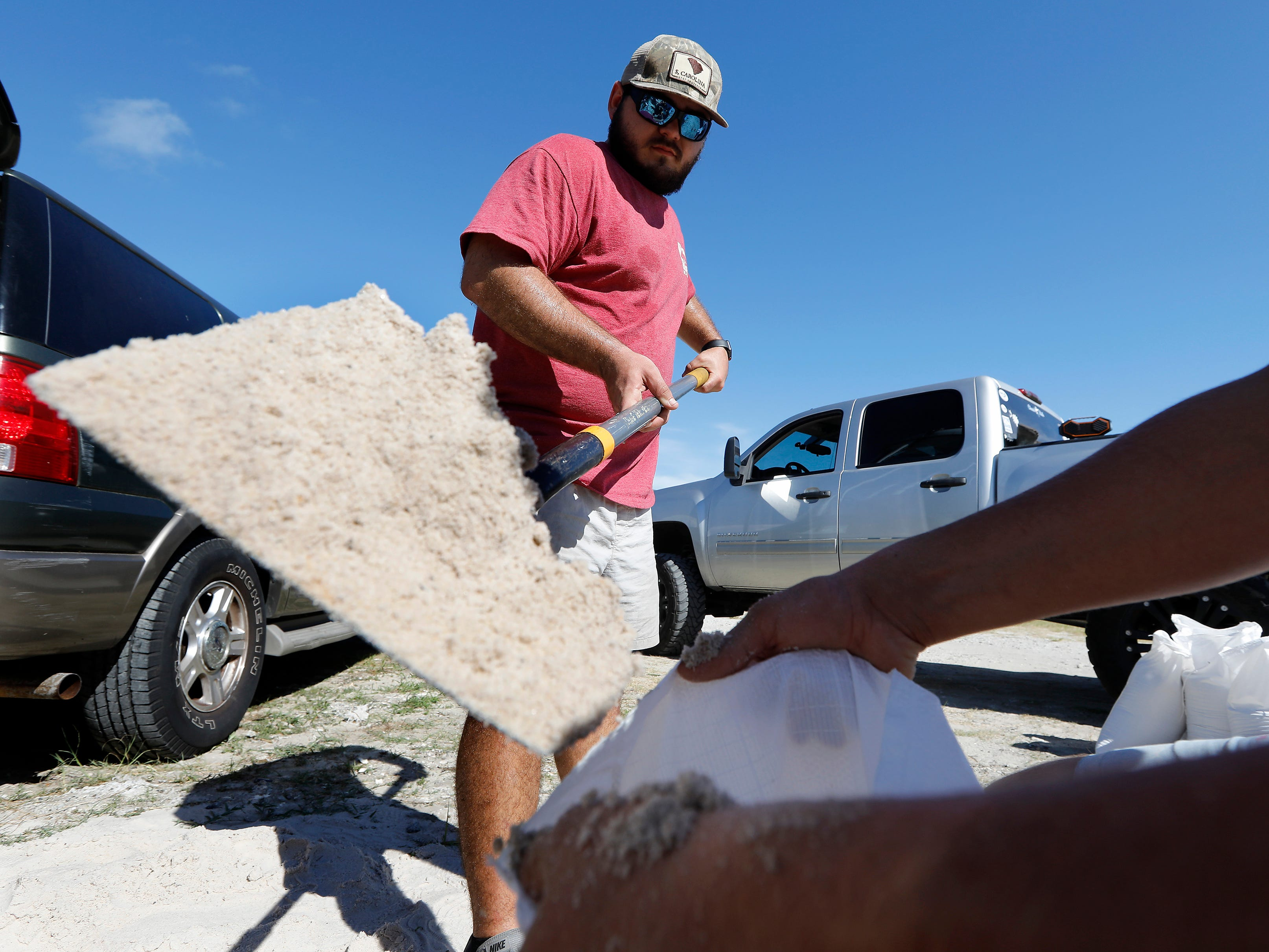Walker Townsend, left, from the Isle of Palms, S.C., fills a sand bag while Dalton Trout holds the bag at the Isle of Palms municipal lot where the city was giving away free sand in preparation for Hurricane Florence at the Isle of Palms S.C., Monday, Sept. 10, 2018.