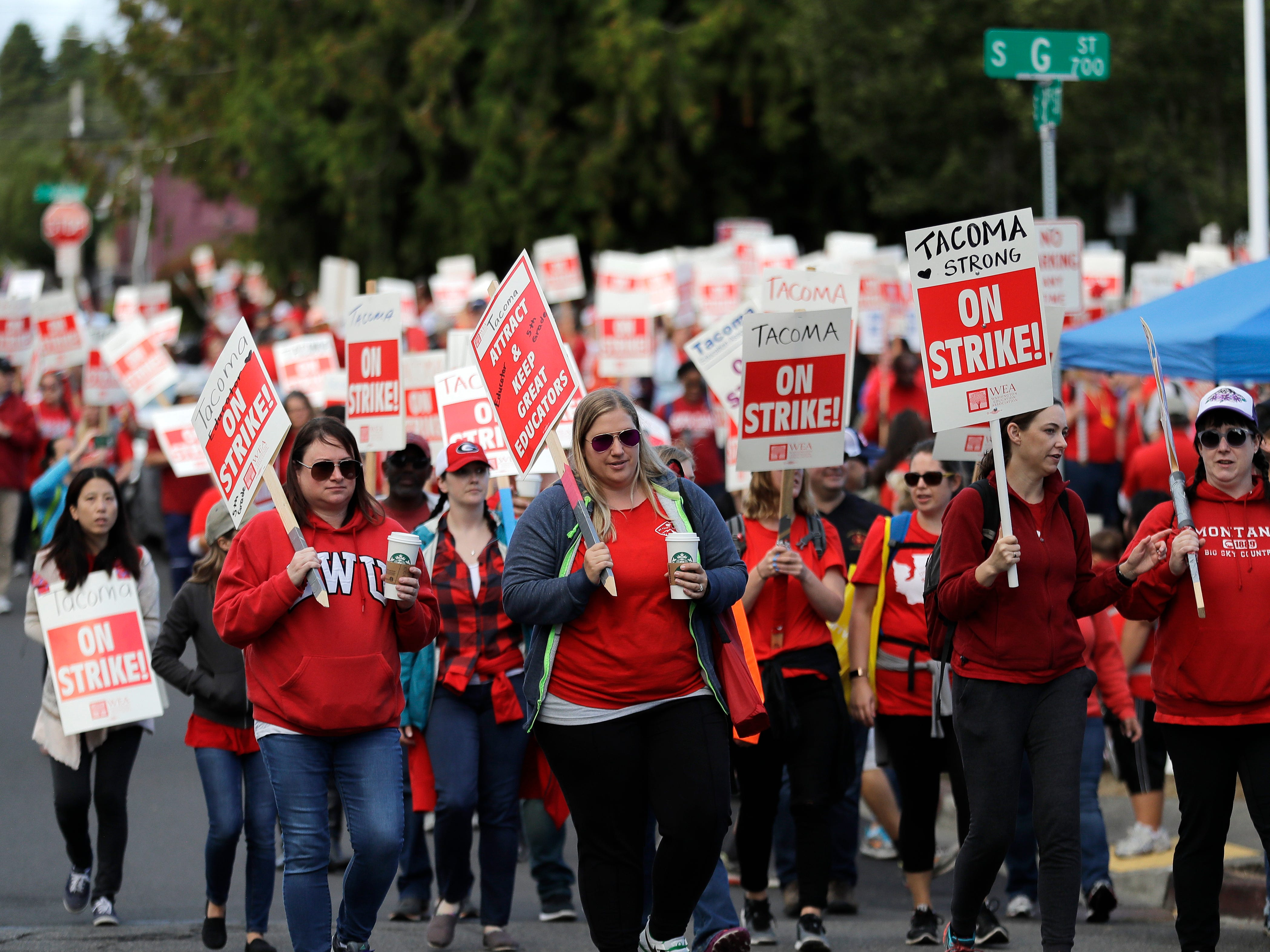 Striking teachers carry picket signs as they march around the Tacoma School District Central Administration Building, Monday, Sept. 10, 2018, in Tacoma, Wash. Teachers in the district have been on strike since last week.