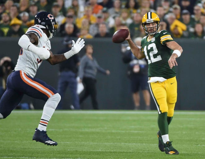 Green Bay Packers quarterback Aaron Rodgers (12) gets pressure from Chicago Bears linebacker Leonard Floyd (94) in the first quarter at Lambeau Field.