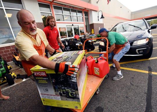 Jim Craig, David Burke and Chris Rayner load generators as people buy supplies at The Home Depot on Sept. 10, 2018, in Wilmington, N.C.