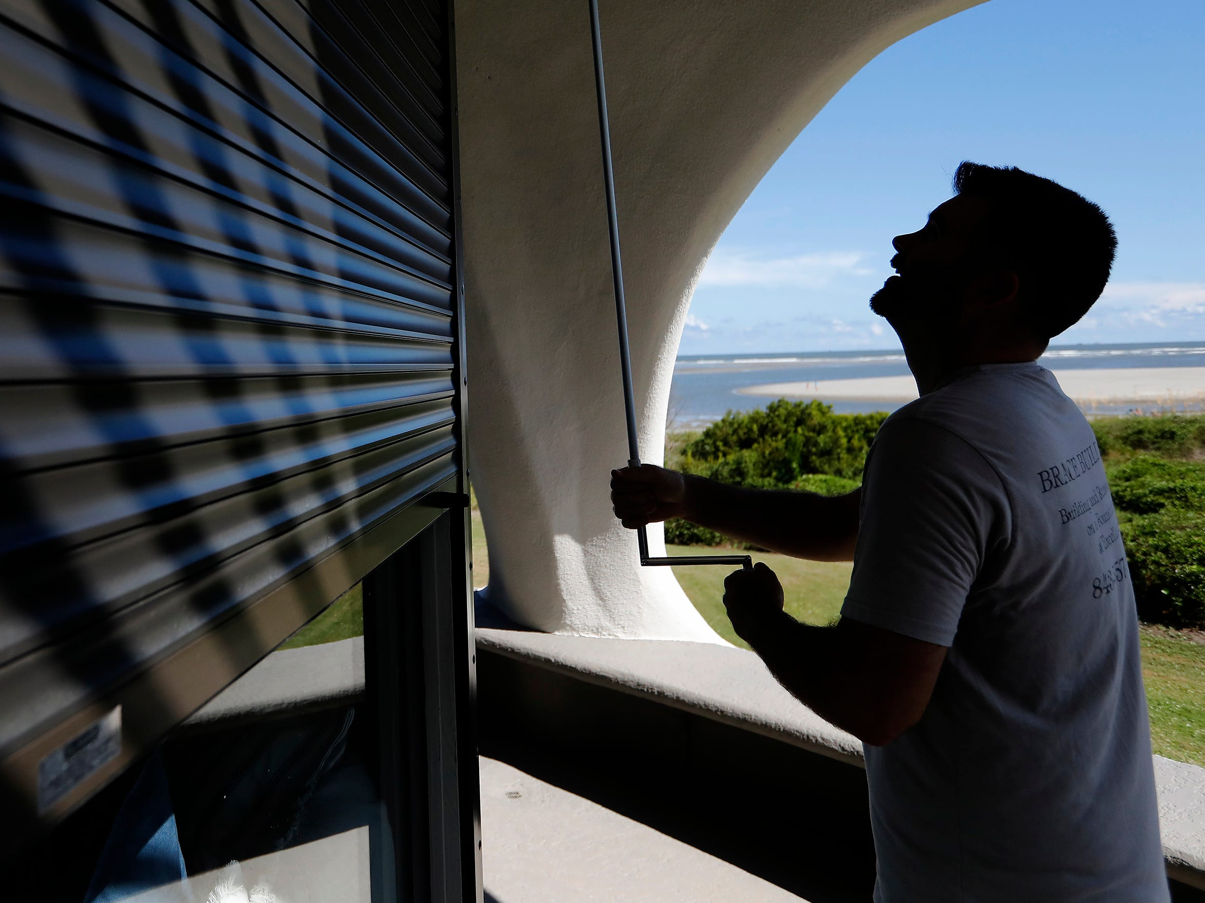 Chris Brace, from Charleston, S.C. lowers hurricane shutters on a client's house in preparation for Hurricane Florence at Sullivan's Island, S.C., Monday, Sept. 10, 2018. Brace said that after S.C. Gov. Henry McMaster ordered an evacuation the property owner asked for the house to be boarded up.