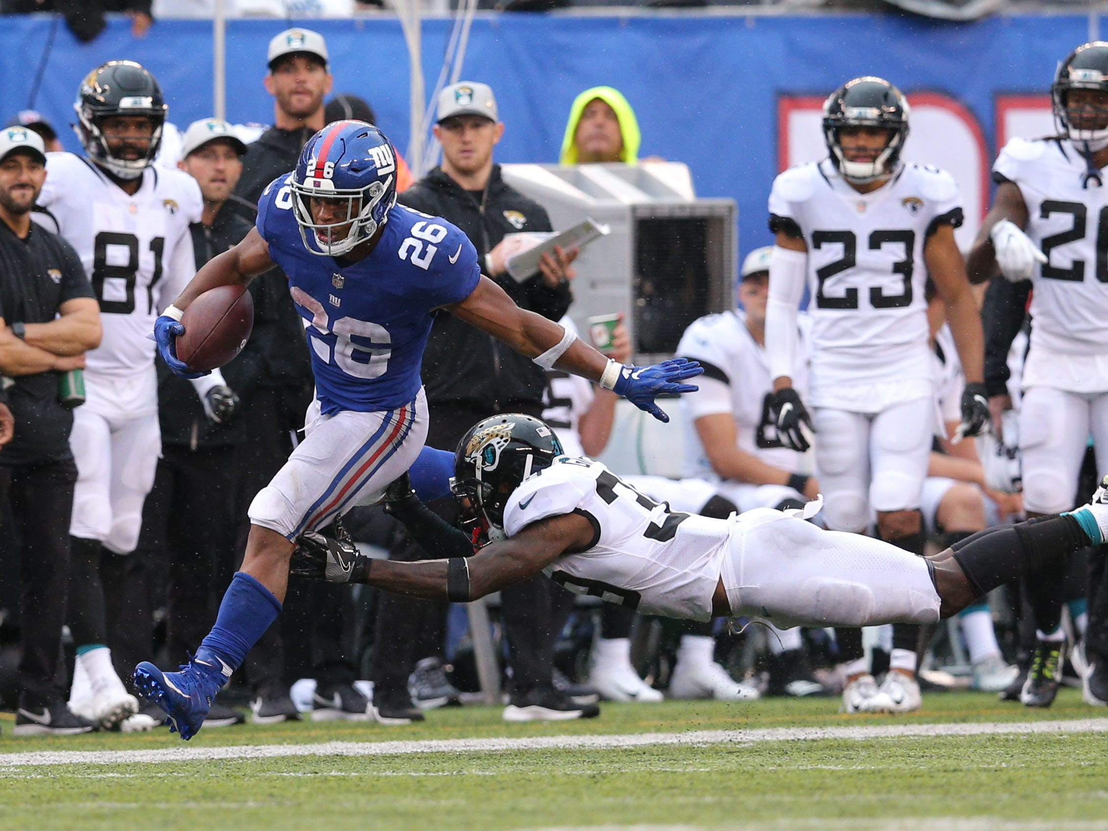 Sep 9, 2018; East Rutherford, NJ, USA; New York Giants running back Saquon Barkley (26) runs for a touchdown against Jacksonville Jaguars defensive back Tashaun Gipson (39) during the fourth quarter at MetLife Stadium. The touchdown was the first of his NFL career. Mandatory Credit: Brad Penner-USA TODAY Sports