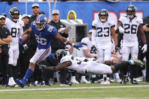 Sep 9, 2018; East Rutherford, NJ, USA; New York Giants running back Saquon Barkley (26) runs for a touchdown against Jacksonville Jaguars defensive back Tashaun Gipson (39) during the fourth quarter at MetLife Stadium. The touchdown was the first of his NFL career. Mandatory Credit: Brad Penner-USA TODAY Sports - Packers QB Carted Off In Clash With Bears