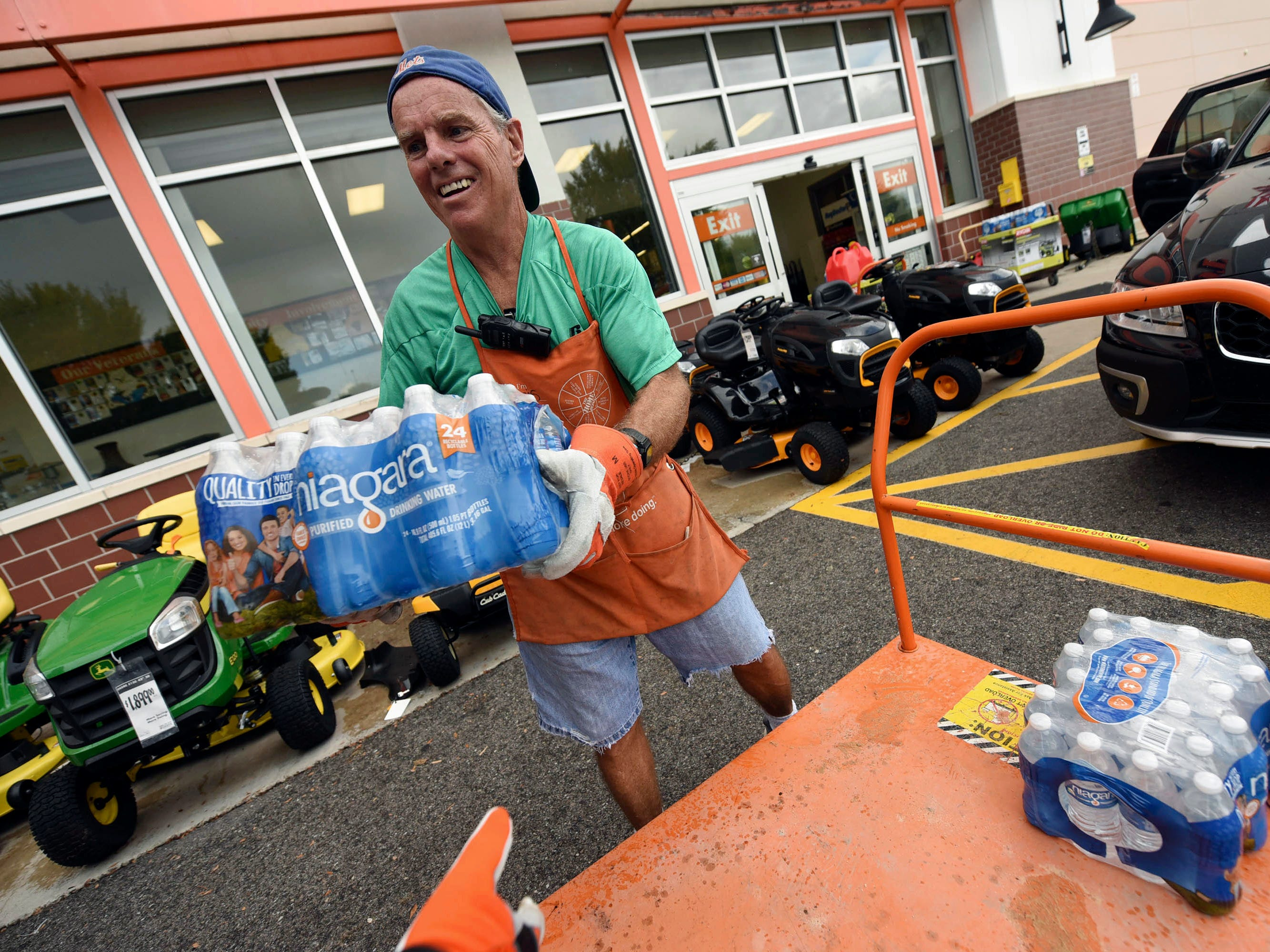 Chris Rayner helps customers load their cars as they buy supplies at The Home Depot on Monday, Sept. 10, 2018, in Wilmington, N.C. Hurricane Florence rapidly strengthened into a potentially catastrophic hurricane on Monday as it closed in on North and South Carolina, carrying winds and water that could wreak havoc over a wide stretch of the eastern United States later this week.