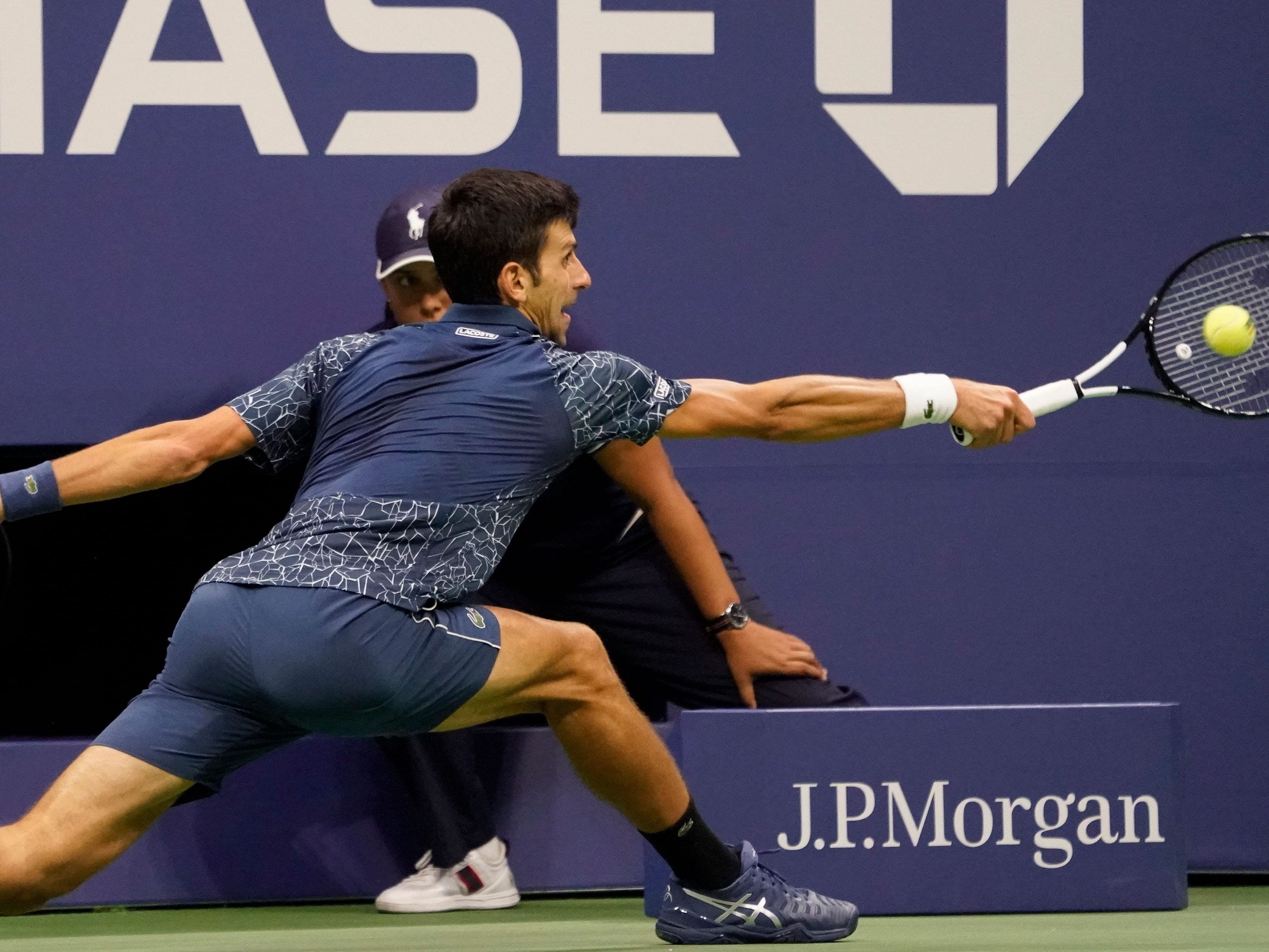 Novak Djokovic stretches for a backhand return against Juan Martin del Potro.