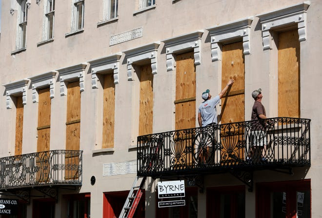 Derek Mundy, left, and Kris Crouse boards up the Confederate House in preparation for Hurricane Florence in downtown Charleston, S.C., Tuesday, Sept. 11, 2018.