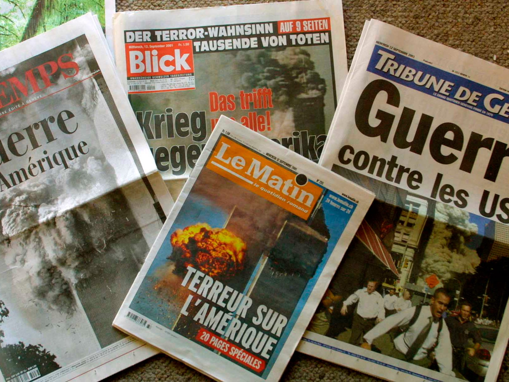 "The front pages of Swiss newspapers are seen Wednesday Sept. 12, 2001 in Geneva, Switzerland. Headlines read ""War in America"", ""Terror against America"" and ""War against the US"".  (AP Photo/Donald Stampfli)"