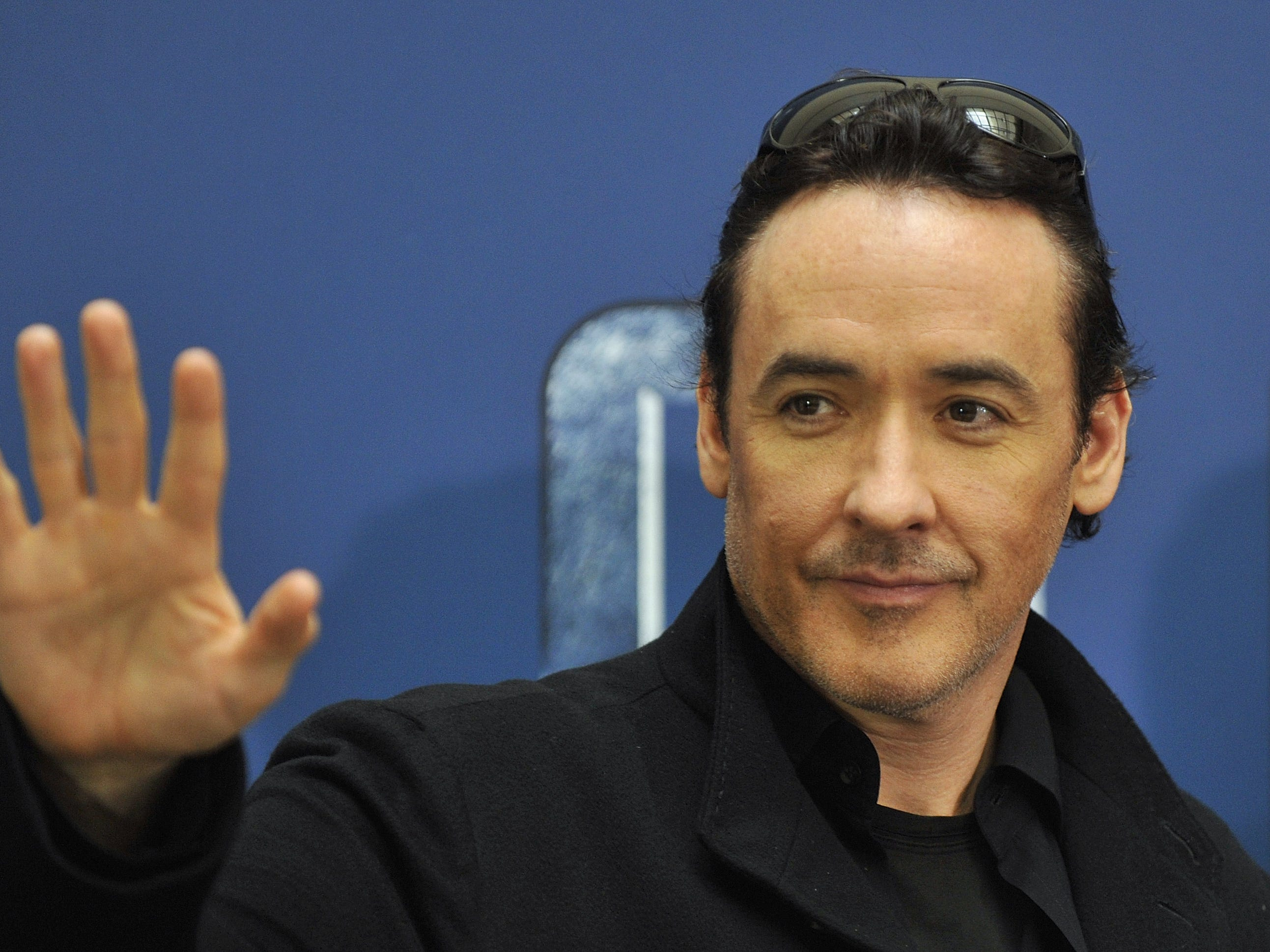 "John Cusack gestures during a photo call for the movie ""2012"" in Berlin, Sept. 28, 2009."