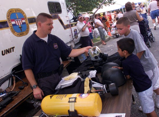 In September 2004, Howell Police Detective Richard Conte shows Trevor Soto, 6, and Zach Lussier, 10, some of the equipment his team uses for emergencies at Howell Day held in Oak Glen Park.