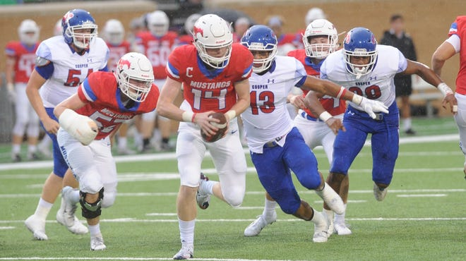 Cooper's Tavian Bonds (13) and Aeneas Favors, right, pressure Grapevine quarterback Cade Rhodes during the first quarter. The Mustangs beat Cooper 31-13 in the nondistrict game at Apogee Stadium in Denton.