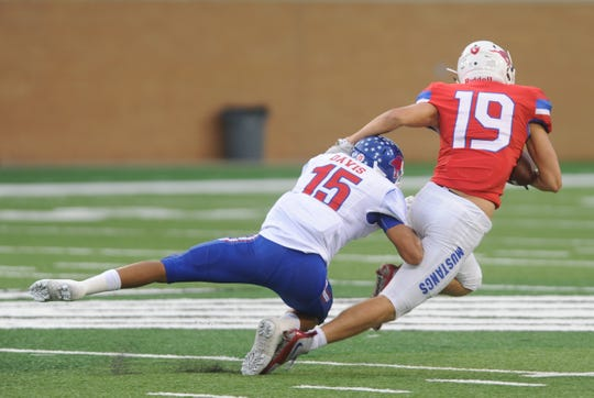 Cooper's Dylon Davis (15) tackles Grapevine's Jack Ertz after a catch in the first quarter. The Mustangs beat Cooper 31-13 in the nondistrict game Friday at Apogee Stadium in Denton.