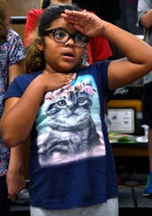 Ruby Ochoa, a fourth-grader at Taylor Elementary School, salutes and holds her hand over her heart while singing the Star Spangled Banner with classmates in remembrance of the 9/11 terrorist attacks, on Tuesday.