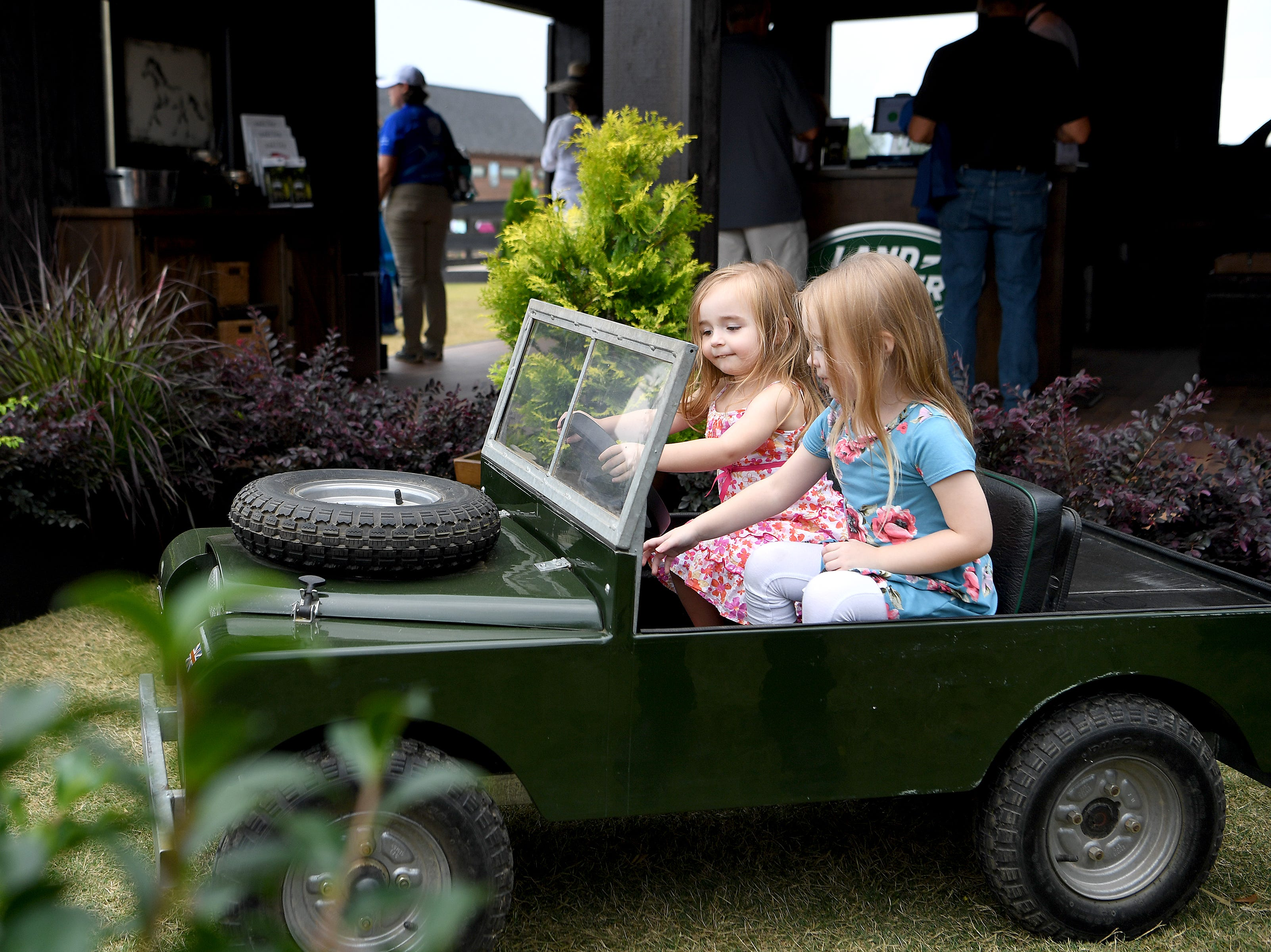Lucy Tate, 2, and her sister, Daily, 3, of Mills Spring, try out a Land Rover that is just their size before the start of the opening ceremonies of the FEI World Equestrian Games at the Tryon International Equestrian Center on Sept. 11, 2018.