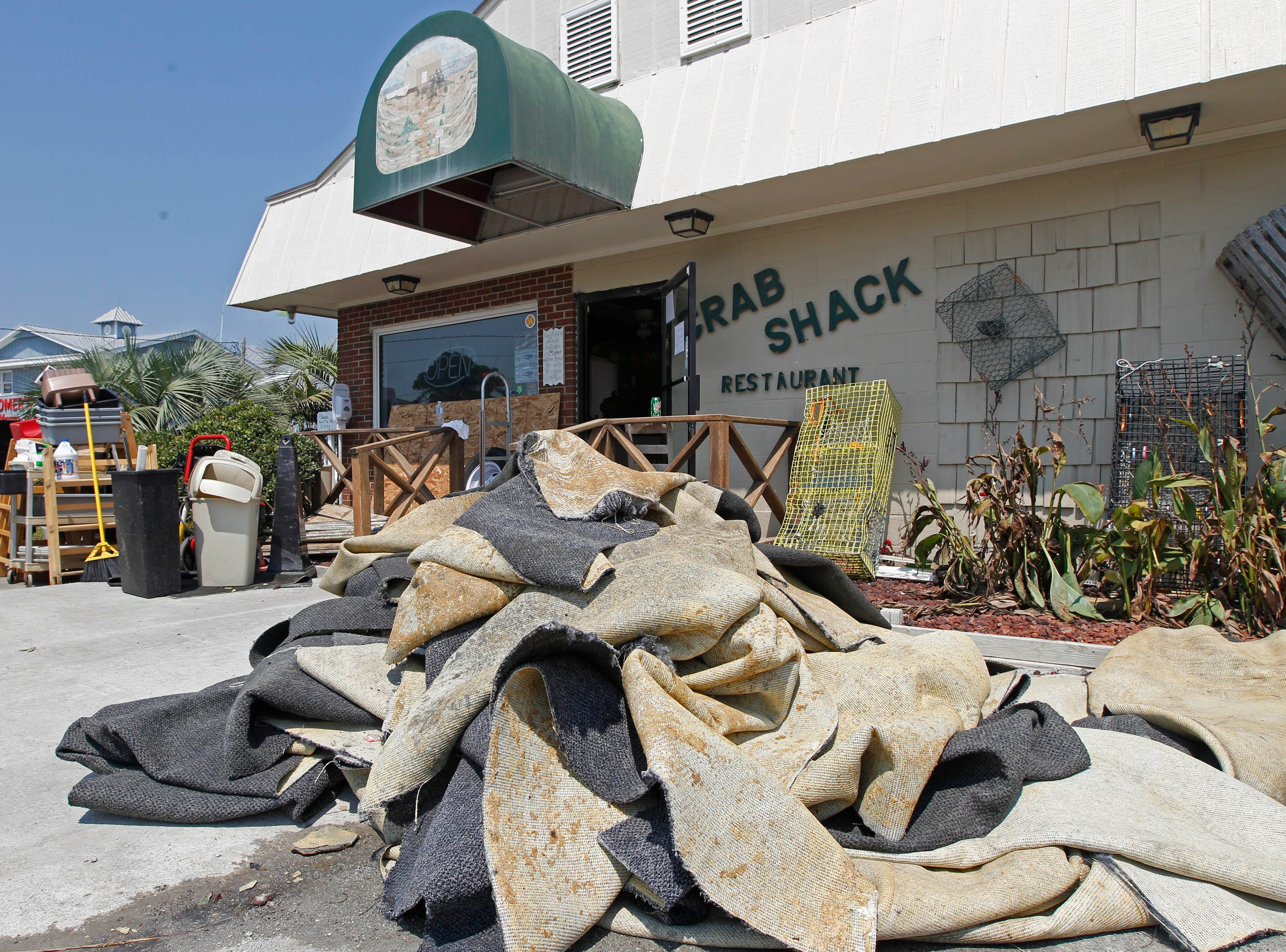 Water-soaked carpet and furniture sit outside the Crab Shack restaurant in Salter Path, N.C., Monday, Aug. 29, 2011. As more roads opened and the power came back two days after Hurricane Irene swept through, people who depend on tourists for their livelihoods had no guarantee whether visitors would come for summer's traditional last hurrah. (AP Photo/Chuck Burton)