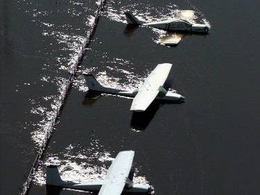 Floodwaters from the Tar River rush past parked planes at the airport in Greenville, N.C., Saturday, Sept. 18, 1999.