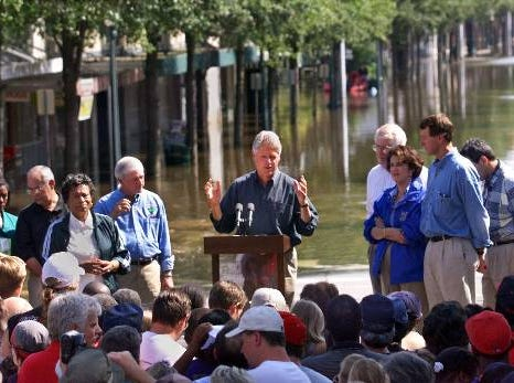 "After an inspection of flood damage wrought by Hurricane Floyd, President Clinton speaks to the people of Tarboro, N.C., one of the hardest hit areas of the state, Monday, Sept. 20, 1999. After seeing entire communities submerged in water, Clinton promised Monday that ""the American family"" would do all it can to help the victims of floods caused by Hurricane Floyd. ""We're going to be with you every step of the way,"" he said. Standing to each side of the president are Tarboro Mayor Donald Morris, right, North Carolina Gov. James Hunt, left, and other community leaders on a stage near Main and Church streets in downtown Tarboro."