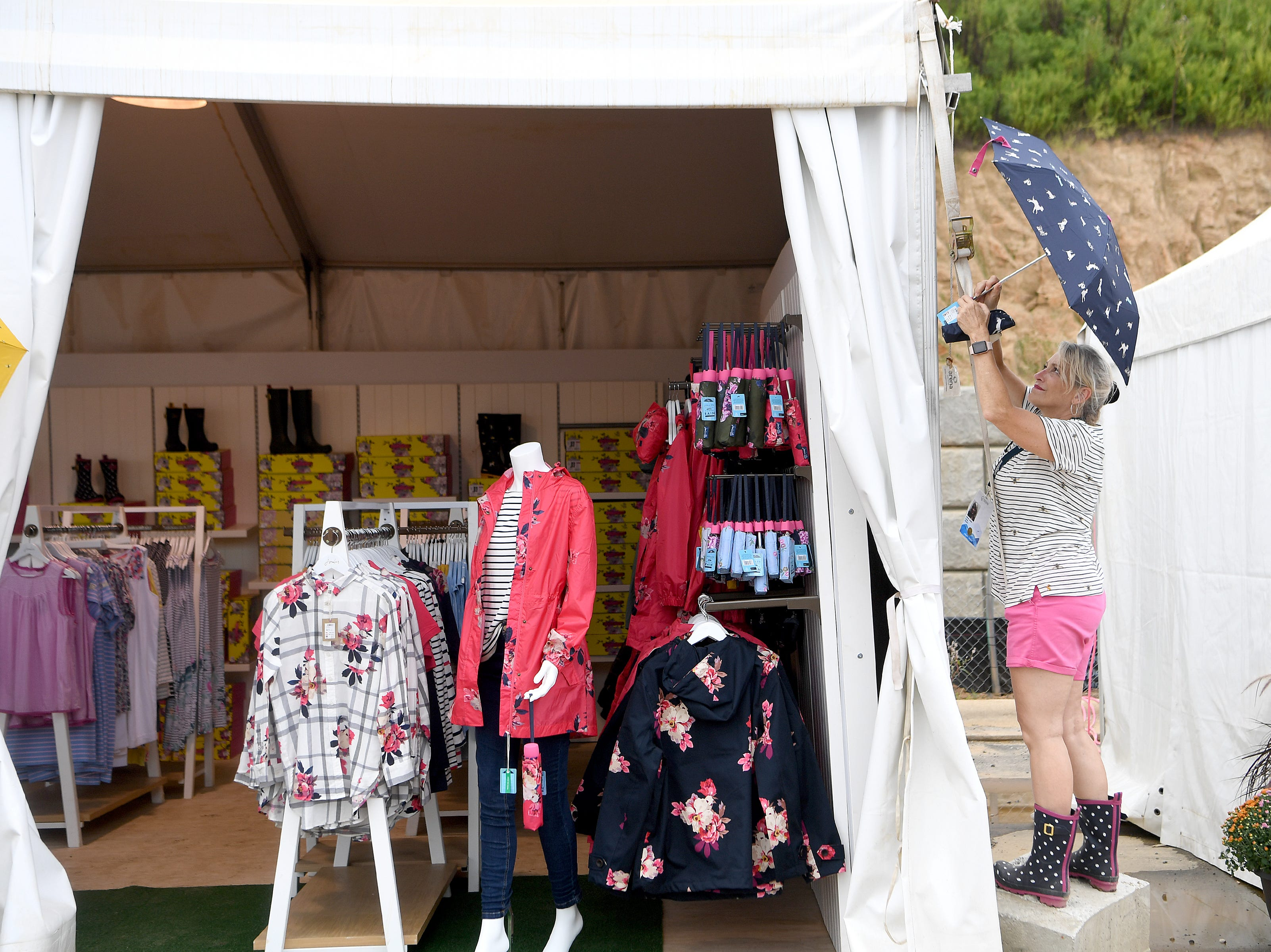 Renee Jones, of Charlotte, hangs an umbrella on the Joules tent, sponsored by Dillards, before the start of the opening ceremonies of the FEI World Equestrian Games at the Tryon International Equestrian Center on Sept. 11, 2018.