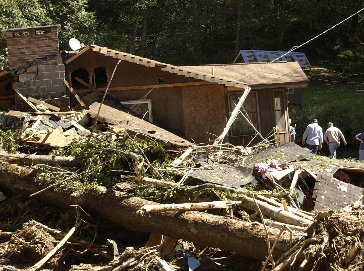 People walk around a heavily damaged house in the Peeks Creek community on Sept 18, 2004, as recovery begins for the area devastated by flooding from Hurricane Ivan.