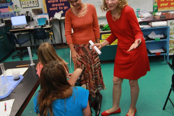 North Carolina First Lady Kristin Cooper (right) and Chief Academic Officer Lisa Gahagan speak with student inside a Madison Middle School science classroom.