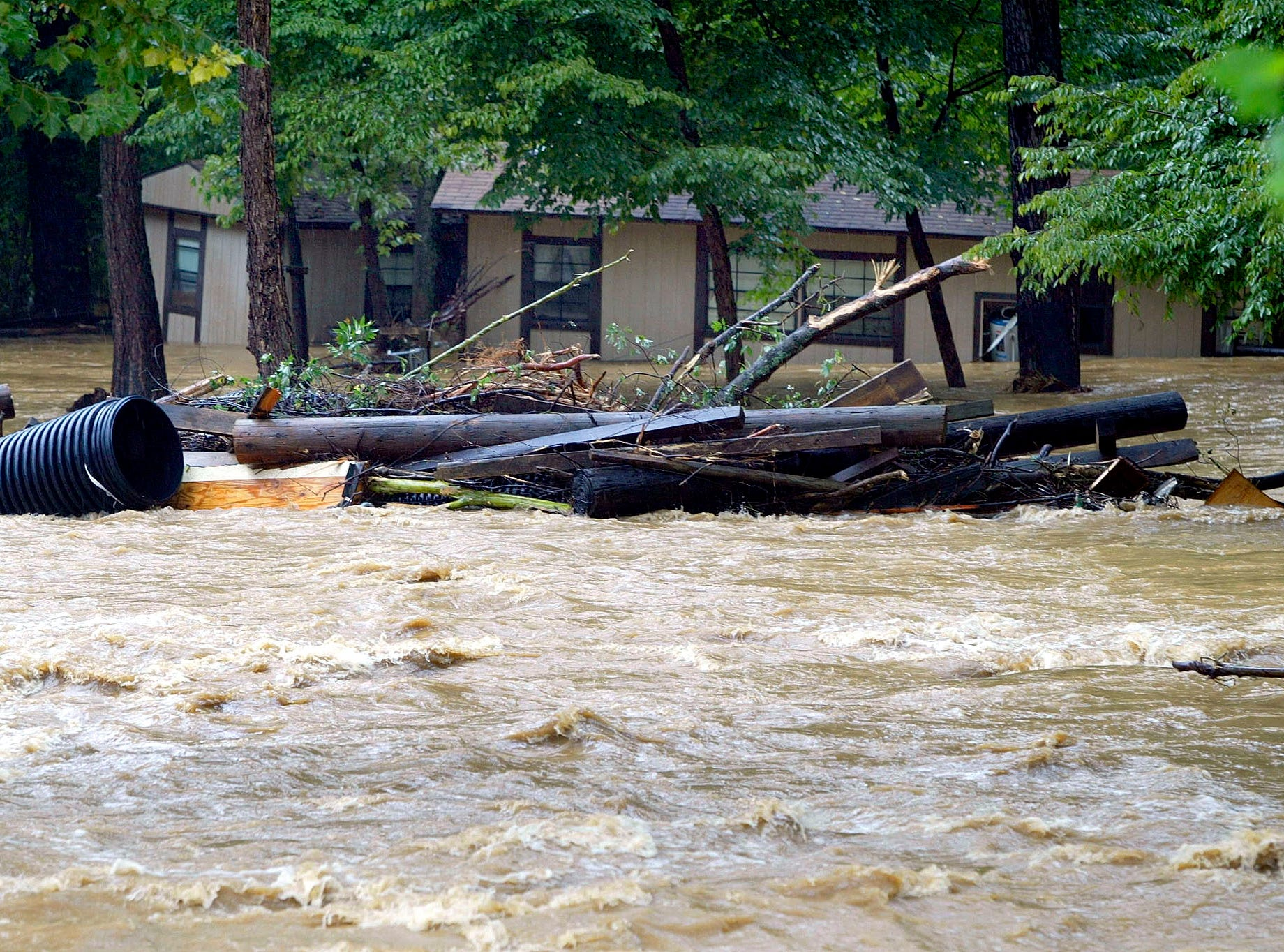 Debris piles up as floodwaters from the Swannanoa River flow past a mobile home in Swannanoa on Sept. 8, 2004. Heavy rains from the remnants of Hurricane Frances caused flooding in the area.