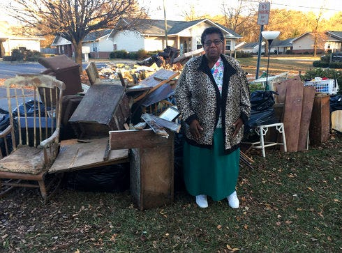 In this Dec. 1, 2016, file photo, Dianne Hines stands in front of the mound of furniture and other belongings pulled from her home after Hurricane Matthew, in Princeville, N.C. Hines' home was rebuilt after Hurricane Floyd in 1999. The town of Princeville is an historic African-American town destroyed by hurricane-induced floods twice in 17 years.