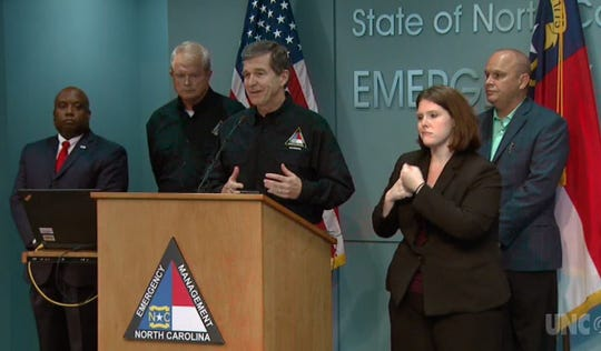 Flanked by N.C. Director of Emergency Management Mike Sprayberry to his immediate left, other state officials and a sign language interpreter, Gov. Roy Cooper describes expected impacts from Hurricane Florence during a press conference Tuesday in Raleigh in this image taken from a UNC-TV livestream of the event.