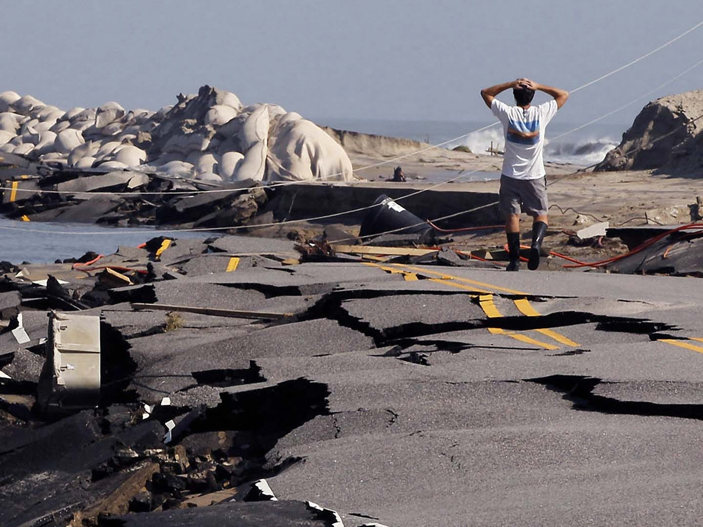A man stares in disbelief at the destruction to N.C. Highway 12 on the north edge of town, Aug. 28, 2011, in Rodanthe, N.C. From North Carolina to New Jersey, Hurricane Irene's winds and storm surge fell short of the doomsday predictions. But the danger is far from over: With rivers still rising, severe flooding is feared across much of the East Coast over the next few days.