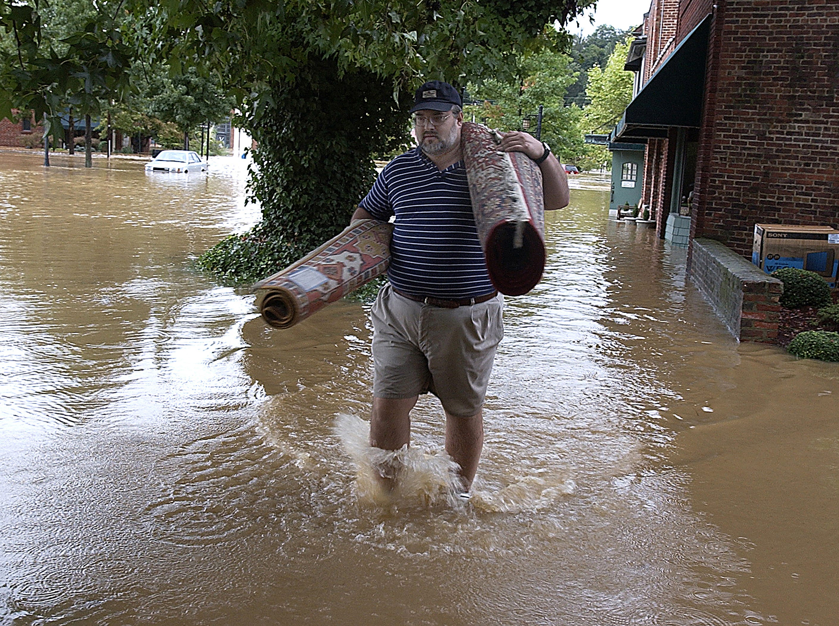 David Ballew carries undamaged area carpets from the Jos. A. Banks store in Biltmore Village after floodwaters from Hurricane Frances flooded Biltmore Village on Sept. 8, 2004.