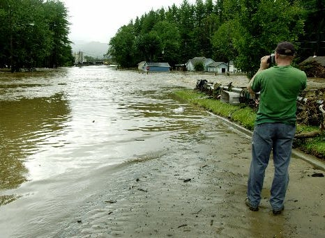 Jeff Edwards takes a picture of a flood street in Canton, N.C., Friday, Sept. 17, 2004. At least three people were dead Friday as heavy wind and flooding rain from the remnants of Hurricane Ivan raked western North Carolina, re-flooding many of the same places hit last week by the remnants of Hurricane Frances.